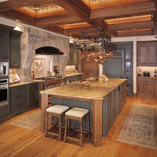 Idéer för ett stort lantligt kök, med en rustik diskho, luckor med upphöjd panel, skåp i slitet trä, granitbänkskiva, flerfärgad stänkskydd, integrerade vitvaror, mellanmörkt trägolv och en köksö