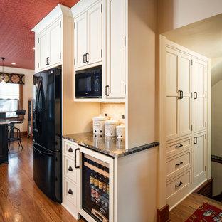 Medium sized rural l-shaped kitchen pantry in Omaha with beaded cabinets, granite worktops, beige splashback, stone tiled splashback, black appliances, medium hardwood flooring, an island, a belfast sink and beige cabinets.
