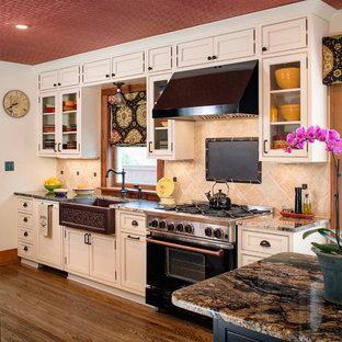 Mid-sized traditional enclosed kitchen appliance - Mid-sized elegant galley medium tone wood floor enclosed kitchen photo in Omaha with a farmhouse sink, beaded inset cabinets, granite countertops, beige backsplash, stone tile backsplash, black appliances, an island and beige cabinets