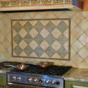 This is an example of a mid-sized mediterranean u-shaped eat-in kitchen in Albuquerque with raised-panel cabinets, green cabinets, granite benchtops, multi-coloured splashback, terra-cotta splashback and stainless steel appliances.