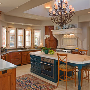 Inspiration for a mediterranean kitchen in San Diego with raised-panel cabinets, medium wood cabinets, marble worktops, white splashback, stone tiled splashback, black appliances, marble flooring, an island and white floors.