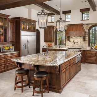 Kitchen - mediterranean u-shaped beige floor kitchen idea in Houston with an undermount sink, raised-panel cabinets, dark wood cabinets, beige backsplash, an island and beige countertops