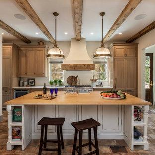 他の地域の広い地中海スタイルのおしゃれなアイランドキッチン (エプロンフロントシンク、フラットパネル扉のキャビネット、グレーのキャビネット、木材カウンター、シルバーの調理設備、テラコッタタイルの床、ピンクの床、ベージュのキッチンカウンター) の写真