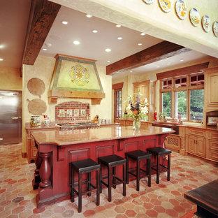 Große Mediterrane Küche in L-Form mit Landhausspüle, Granit-Arbeitsplatte, Rückwand aus Backstein, Küchengeräten aus Edelstahl, Kücheninsel, profilierten Schrankfronten, roten Schränken, Küchenrückwand in Rot und rotem Boden in Kansas City