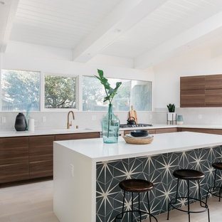 Midcentury modern open concept kitchen inspiration - Example of a 1960s l-shaped light wood floor and beige floor open concept kitchen design in Los Angeles with an undermount sink, flat-panel cabinets, brown cabinets, gray backsplash, stainless steel appliances, an island and white countertops