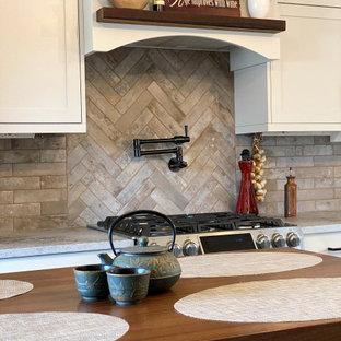 シアトルの中くらいのトランジショナルスタイルのおしゃれなキッチン (アンダーカウンターシンク、シェーカースタイル扉のキャビネット、グレーのキャビネット、クオーツストーンカウンター、グレーのキッチンパネル、レンガのキッチンパネル、シルバーの調理設備、磁器タイルの床、茶色い床、マルチカラーのキッチンカウンター) の写真