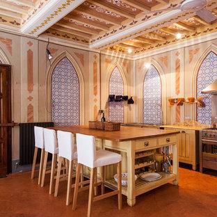 Foto di una cucina a corridoio mediterranea con ante lisce, ante gialle, top in legno, elettrodomestici in acciaio inossidabile, un'isola e pavimento arancione