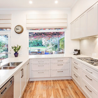 This is an example of a transitional u-shaped eat-in kitchen in Adelaide with a double-bowl sink, shaker cabinets, white cabinets, grey splashback, medium hardwood floors, a peninsula, beige floor and white benchtop.