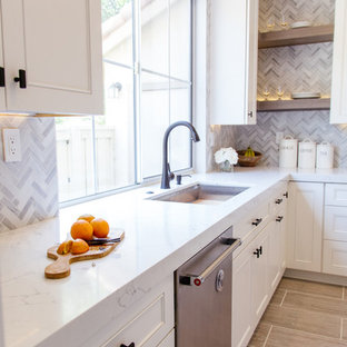 Mid-sized contemporary eat-in kitchen ideas - Eat-in kitchen - mid-sized contemporary l-shaped porcelain tile and gray floor eat-in kitchen idea in Orange County with an undermount sink, shaker cabinets, white cabinets, marble countertops, gray backsplash, an island, mosaic tile backsplash and stainless steel appliances