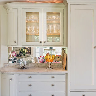 Inspiration for a mid-sized traditional u-shaped eat-in kitchen in Berkshire with a farmhouse sink, shaker cabinets, grey cabinets, limestone benchtops, metallic splashback, mirror splashback, porcelain floors and no island.