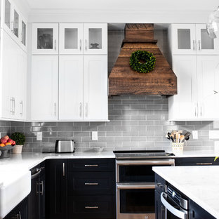 Mid-sized farmhouse eat-in kitchen photos - Mid-sized country l-shaped medium tone wood floor and brown floor eat-in kitchen photo in Charlotte with a farmhouse sink, shaker cabinets, black cabinets, quartz countertops, gray backsplash, subway tile backsplash, stainless steel appliances, an island and white countertops