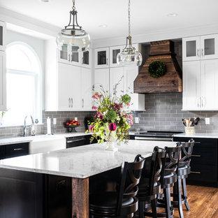 Inspiration för mellanstora, avskilda lantliga vitt l-kök, med en rustik diskho, skåp i shakerstil, bänkskiva i kvarts, grått stänkskydd, stänkskydd i tunnelbanekakel, rostfria vitvaror, mellanmörkt trägolv, en köksö, brunt golv och vita skåp