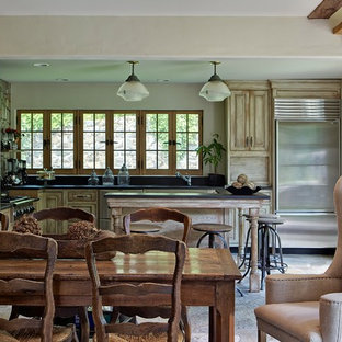 Rustic eat-in kitchen pictures - Inspiration for a rustic l-shaped eat-in kitchen remodel in Denver with raised-panel cabinets, light wood cabinets and stainless steel appliances