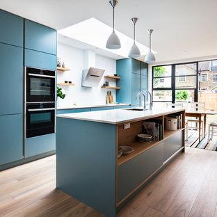 Einzeilige, Große Moderne Wohnküche mit Unterbauwaschbecken, flächenbündigen Schrankfronten, blauen Schränken, Quarzit-Arbeitsplatte, Küchenrückwand in Weiß, Glasrückwand, schwarzen Elektrogeräten, braunem Holzboden und Kücheninsel in London