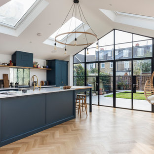 Photo of a medium sized contemporary single-wall open plan kitchen in London with a single-bowl sink, flat-panel cabinets, blue cabinets, marble worktops, an island, brown floors, grey worktops, mirror splashback, stainless steel appliances and light hardwood flooring.
