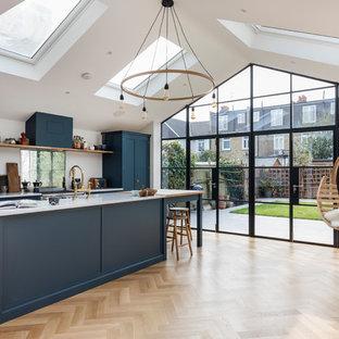 ロンドンの中くらいのコンテンポラリースタイルのおしゃれなキッチン (シングルシンク、フラットパネル扉のキャビネット、青いキャビネット、大理石カウンター、茶色い床、グレーのキッチンカウンター、ミラータイルのキッチンパネル、シルバーの調理設備、淡色無垢フローリング) の写真