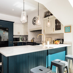 This is an example of a small contemporary u-shaped kitchen in London with white splashback, ceramic splashback, white worktops, beaded cabinets, blue cabinets, granite worktops, a breakfast bar and grey floors.