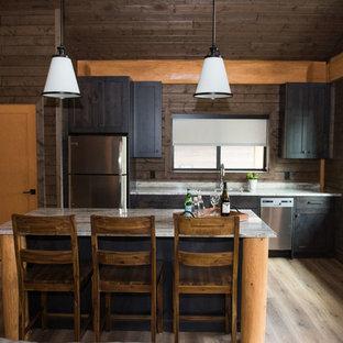 バンクーバーの中サイズのラスティックスタイルのおしゃれなキッチン (ダブルシンク、シェーカースタイル扉のキャビネット、濃色木目調キャビネット、御影石カウンター、ガラスまたは窓のキッチンパネル、シルバーの調理設備の、ラミネートの床、茶色い床、グレーのキッチンカウンター) の写真