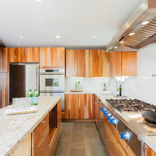 Inspiration for a contemporary kitchen remodel in San Francisco with limestone countertops, stainless steel appliances, flat-panel cabinets, white backsplash and glass sheet backsplash