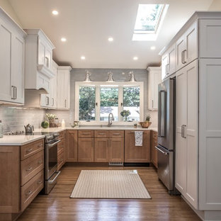 トランジショナルスタイルのおしゃれなコの字型キッチン (シェーカースタイル扉のキャビネット、中間色木目調キャビネット、グレーのキッチンパネル、無垢フローリング、アイランドなし、茶色い床、白いキッチンカウンター) の写真
