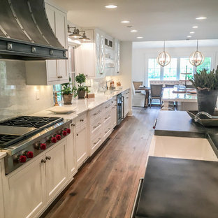Photo of an expansive transitional l-shaped kitchen in Other with a farmhouse sink, beaded inset cabinets, white cabinets, zinc benchtops, white splashback, marble splashback, stainless steel appliances, light hardwood floors, multiple islands and brown floor.