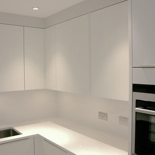 Small contemporary u-shaped separate kitchen in London with a drop-in sink, white cabinets, solid surface benchtops, white splashback, stainless steel appliances and yellow benchtop.