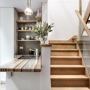 メルボルンのエクレクティックスタイルのおしゃれなキッチン (落し込みパネル扉のキャビネット、白いキャビネット、木材カウンター、茶色いキッチンパネル、石タイルのキッチンパネル、シルバーの調理設備の、マルチカラーのキッチンカウンター) の写真