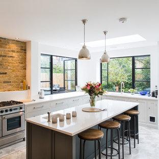Foto de cocina comedor en L, contemporánea, grande, con fregadero integrado, armarios estilo shaker, puertas de armario grises, encimera de acrílico, suelo de terrazo, una isla y electrodomésticos de acero inoxidable