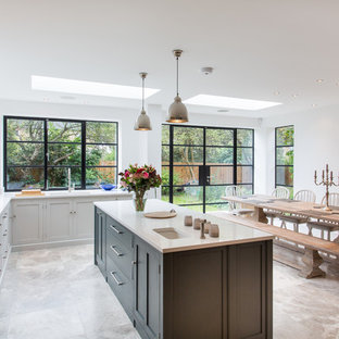 Large contemporary l-shaped kitchen/diner in Surrey with an integrated sink, shaker cabinets, grey cabinets, composite countertops, terrazzo flooring and an island.