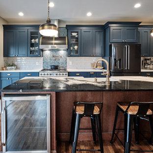 フィラデルフィアの大きいエクレクティックスタイルのおしゃれなキッチン (エプロンフロントシンク、落し込みパネル扉のキャビネット、青いキャビネット、珪岩カウンター、グレーのキッチンパネル、セラミックタイルのキッチンパネル、黒い調理設備、無垢フローリング、茶色い床、マルチカラーのキッチンカウンター) の写真