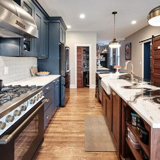 フィラデルフィアの広いエクレクティックスタイルのおしゃれなキッチン (エプロンフロントシンク、落し込みパネル扉のキャビネット、青いキャビネット、珪岩カウンター、グレーのキッチンパネル、セラミックタイルのキッチンパネル、黒い調理設備、無垢フローリング、茶色い床、マルチカラーのキッチンカウンター) の写真