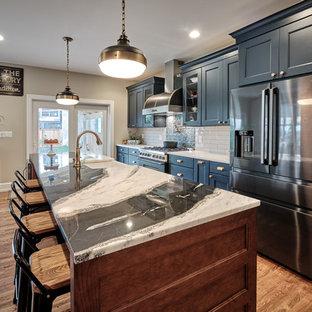 Exempel på ett stort eklektiskt flerfärgad flerfärgat kök, med en rustik diskho, luckor med infälld panel, blå skåp, bänkskiva i kvartsit, grått stänkskydd, stänkskydd i keramik, svarta vitvaror, mellanmörkt trägolv, en köksö och brunt golv