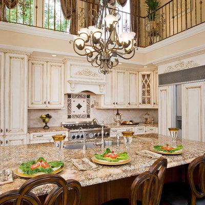 Large elegant l-shaped enclosed kitchen photo in Philadelphia with granite countertops, brown countertops, an undermount sink, raised-panel cabinets, beige cabinets, beige backsplash, travertine backsplash, paneled appliances and an island