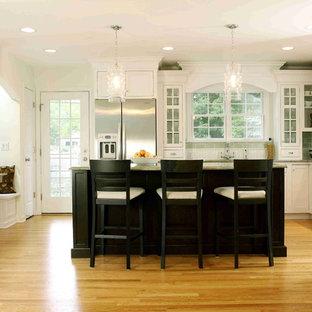 Große Klassische Wohnküche in L-Form mit Schrankfronten im Shaker-Stil, Küchengeräten aus Edelstahl, weißen Schränken, Küchenrückwand in Grün, Rückwand aus Metrofliesen, Granit-Arbeitsplatte, Kücheninsel, braunem Holzboden und grüner Arbeitsplatte in Chicago
