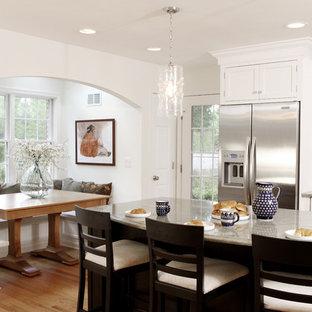 Ejemplo de cocina comedor tradicional, grande, con armarios estilo shaker, puertas de armario blancas, electrodomésticos de acero inoxidable, encimera de granito, una isla y suelo de madera en tonos medios