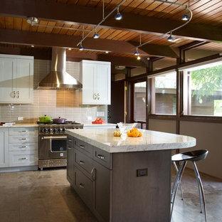 Foto på ett avskilt, mellanstort funkis l-kök, med en rustik diskho, skåp i shakerstil, vita skåp, rostfria vitvaror, en köksö, marmorbänkskiva, beige stänkskydd, stänkskydd i porslinskakel och travertin golv