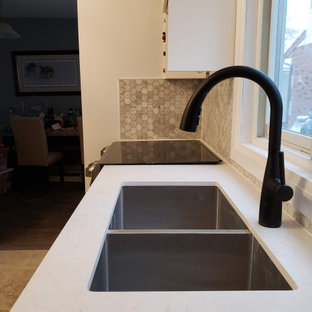 トロントの中サイズのシャビーシック調のおしゃれなキッチン (アンダーカウンターシンク、シェーカースタイル扉のキャビネット、白いキャビネット、珪岩カウンター、グレーのキッチンパネル、大理石のキッチンパネル、黒い調理設備、大理石の床、アイランドなし、白いキッチンカウンター) の写真