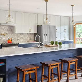 На фото: большая параллельная кухня в стиле неоклассика (современная классика) с фасадами в стиле шейкер, синими фасадами, столешницей из кварцевого агломерата, фартуком из цементной плитки, техникой из нержавеющей стали, светлым паркетным полом, островом и белой столешницей с