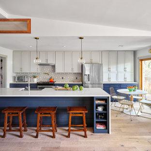 Klassisk inredning av ett stort vit vitt parallellkök, med skåp i shakerstil, blå skåp, bänkskiva i kvarts, stänkskydd i cementkakel, rostfria vitvaror, ljust trägolv och en köksö