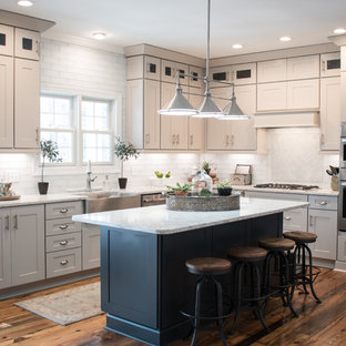 Large contemporary l-shaped kitchen pantry in Raleigh with a farmhouse sink, white splashback, stainless steel appliances, medium hardwood floors, white benchtop, shaker cabinets, white cabinets, marble benchtops, with island, glass tile splashback and multi-coloured floor.