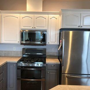 Amerikansk inredning av ett mellanstort beige beige kök, med en dubbel diskho, skåp i shakerstil, vita skåp, kaklad bänkskiva, beige stänkskydd, stänkskydd i stenkakel, rostfria vitvaror, laminatgolv, en köksö och brunt golv