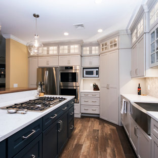 Large traditional l-shaped kitchen in Providence with a farmhouse sink, recessed-panel cabinets, white cabinets, quartz benchtops, multi-coloured splashback, limestone splashback, stainless steel appliances, dark hardwood floors, with island, brown floor and white benchtop.