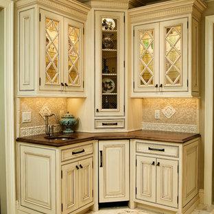 ニューアークの広いトラディショナルスタイルのおしゃれなアイランドキッチン (アンダーカウンターシンク、インセット扉のキャビネット、ベージュのキャビネット、御影石カウンター、ベージュキッチンパネル、セラミックタイルのキッチンパネル、シルバーの調理設備、大理石の床) の写真