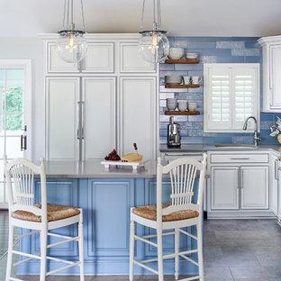 Klassisk inredning av ett mellanstort grå grått kök, med en undermonterad diskho, luckor med upphöjd panel, vita skåp, bänkskiva i kvarts, blått stänkskydd, stänkskydd i porslinskakel, integrerade vitvaror, laminatgolv, en köksö och grått golv