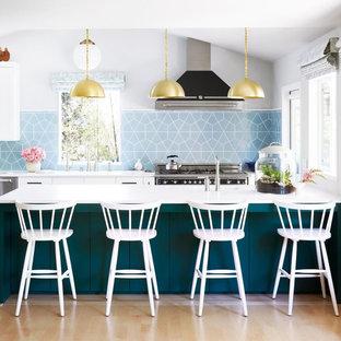 Moderne Küche mit Quarzit-Arbeitsplatte, Küchenrückwand in Blau, Küchengeräten aus Edelstahl, Kücheninsel und weißer Arbeitsplatte in Minneapolis