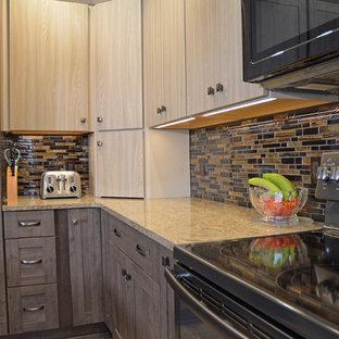 他の地域の小さいトランジショナルスタイルのおしゃれなキッチン (アンダーカウンターシンク、フラットパネル扉のキャビネット、グレーのキャビネット、クオーツストーンカウンター、茶色いキッチンパネル、ガラスタイルのキッチンパネル、黒い調理設備、クッションフロア、ベージュの床、ベージュのキッチンカウンター) の写真