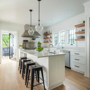 Esempio di una cucina tradizionale di medie dimensioni con lavello sottopiano, ante in stile shaker, ante bianche, paraspruzzi a effetto metallico, elettrodomestici in acciaio inossidabile, parquet chiaro, isola, pavimento beige e top in quarzite
