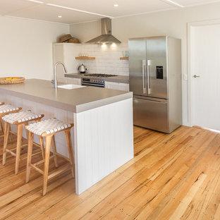 ネイピアの小さいシャビーシック調のおしゃれなキッチン (エプロンフロントシンク、落し込みパネル扉のキャビネット、白いキャビネット、クオーツストーンカウンター、白いキッチンパネル、セラミックタイルのキッチンパネル、シルバーの調理設備の、無垢フローリング、茶色い床、グレーのキッチンカウンター) の写真