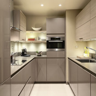 Enclosed kitchen - small modern u-shaped beige floor enclosed kitchen idea in New York with flat-panel cabinets, light wood cabinets, gray backsplash, stainless steel appliances, no island and gray countertops