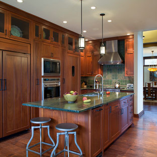 Arts and crafts u-shaped kitchen in Other with an undermount sink, shaker cabinets, dark wood cabinets, green splashback, panelled appliances, dark hardwood floors, with island and green benchtop.